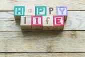 Wooden block word is HAPPY life on wooden background — Foto de Stock
