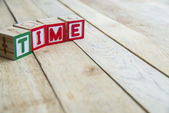 Wooden blocks are Time word on wooden floor — Stock fotografie