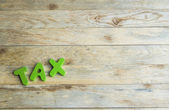 Colorful wooden word Tax on wooden floor — Stock Photo