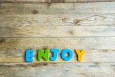 Colorful wooden word Enjoy on wooden floor3 — Stock Photo