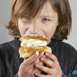 Young boy enjoying cream bun with almond paste — Stock Photo #12403694