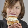Young boy with a cream bun with almond paste — Stock Photo #12403700