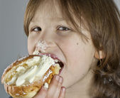 Boy enjoying a cream bun with almond paste — Photo