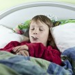 Boy in bed with thermometer — Stock Photo