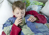 Young boy in bed taking his medicin — Stock Photo