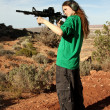 Teenage girl shooting at targets of ranch. - Stock Photo