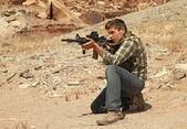 Teenage boy shooting rifle. — Stock Photo