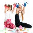 Two happy girls playing with finger colours on white background — Foto Stock