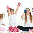 Three happy girls playing with finger colours on white backgroun — Stock Photo