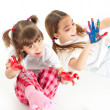 Two happy girls playing with finger colours on white background — Stock Photo