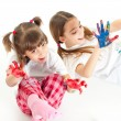 Two happy girls playing with finger colours on white background — Stock Photo #12460375