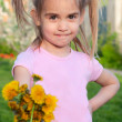 Happy little girl holding out flowers spring outdoor portrait — Stock Photo