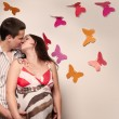 Stock Photo: Young caucasian pregnant couple kissing near the wall with paper