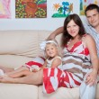 Happy young family on sofa in home - Stock Photo