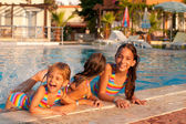 Three little girls playing and splashing in the pool — Stock Photo