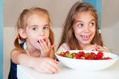 Cute little girls eating strawberry — Stock Photo