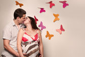 Young caucasian pregnant couple kissing near the wall with paper — Stock Photo