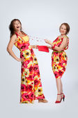 Two beautiful fashionable women in multicoloured dresses. Studio — Stock Photo