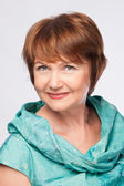 Beautiful fashionable smiling mature woman in turquoise costume — Stock Photo