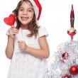 Happy Little Girl Wearing Santa Hat with heart form lollipop by — Stock Photo