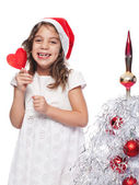 Happy Little Girl Wearing Santa Hat with heart form lollipop by — Stock Photo