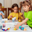 Three little girls (sisters) painting on Easter eggs - Stock Photo