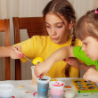 Two little girls (sisters) painting on Easter eggs — Stock Photo