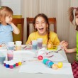 Stock Photo: Three little girls (sisters) painting on Easter eggs