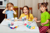 Three little girls (sisters) painting on Easter eggs — Stock Photo