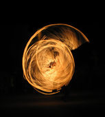 Girl performing fire dance in the night; silhouette — Stock Photo