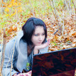 Young woman in the forest with notebook — Stock Photo
