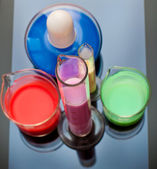 Tubes, bulb and measuring glass with colorful liquids — Stock Photo