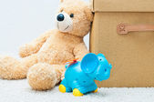 Toy bear and clockwork elephant with brown textile box with hand — Stock Photo