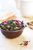 Green tea leaves with rose buds — Stock Photo
