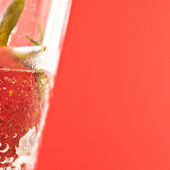 Strawberry immersed in fizzy water in a glass — Stock Photo