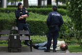 Vienna policemen inspecting a man laying on the ground — Stock Photo