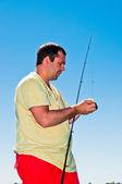 Fisherman with fishing rod — Stock Photo