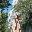 Beautiful woman walking in front of the city park — Stock Photo #30060391