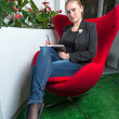 Secretary girl in office with red chair — Stockfoto