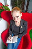 Dziewczyna sekretarz w biurze z czerwone krzesło — Zdjęcie stockowe