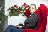 секретарь девушка в офисе с красный стул — Стоковое фото
