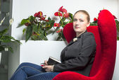 Secretary girl in office with red chair — Stock Photo
