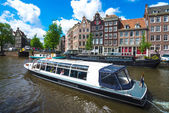 Tour boat on Amsterdam canal — Stock Photo