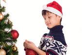 Jongen aankleedt kerstboom — Stockfoto
