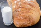 面包和牛奶在桌子上的玻璃 — 图库照片