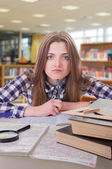 Schoolgirl is tired of studying in library — Stockfoto