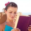 Pretty young female reading a book while lying by the beach - Foto Stock