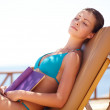 Young beautiful woman on the beach relaxing and reading book - Stock Photo