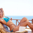 Young beautiful woman on the beach relaxing and reading book - Foto Stock