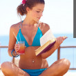 Young beautiful woman reads book on the beach and making yoga - Foto de Stock